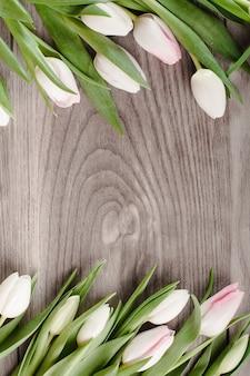 Marco de tulipanes brillantes sobre madera