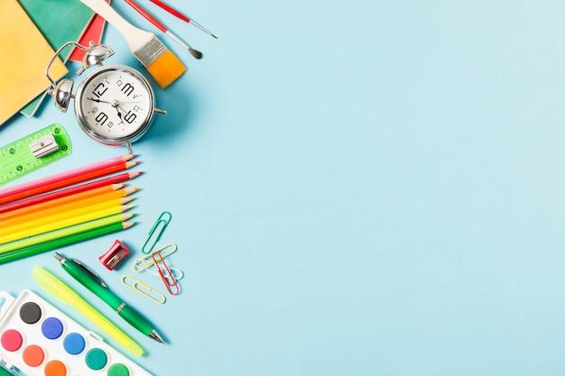 Marco de útiles escolares sobre fondo azul claro