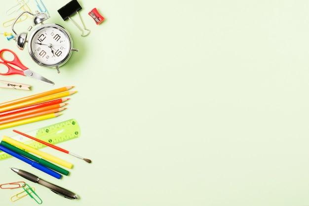 Marco de útiles escolares sobre fondo verde claro