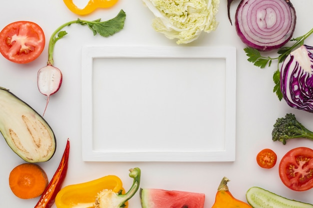 Marco vacío blanco con arreglo de verduras