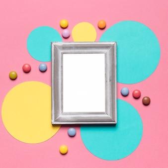Un marco vacío en blanco con borde plateado en marco circular con gemas de colores sobre el fondo rosa