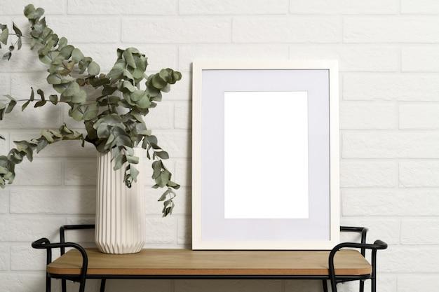 Marco vacío blanco en estante con planta en florero