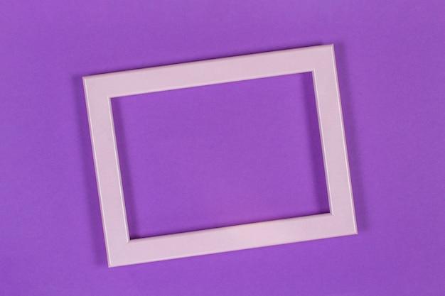 Marco vacío en blanco sobre fondo de papel de color púrpura violeta