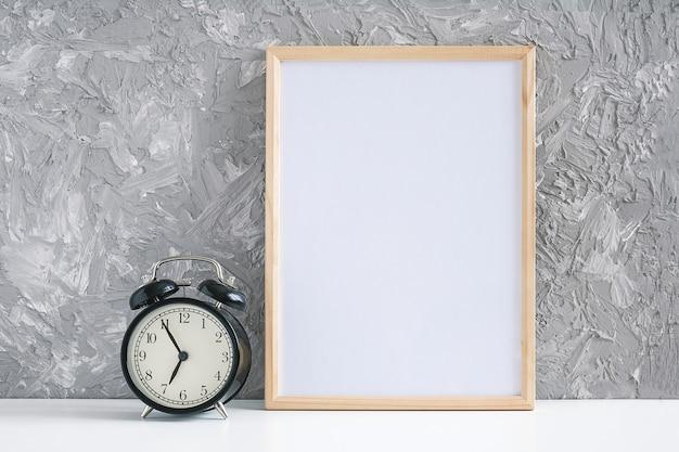 Marco vacío blanco vertical de madera y despertador negro en la tabla en fondo gris del muro de cemento.