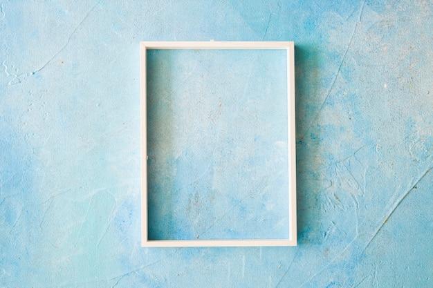 Un marco vacío con borde blanco en la pared pintada de azul