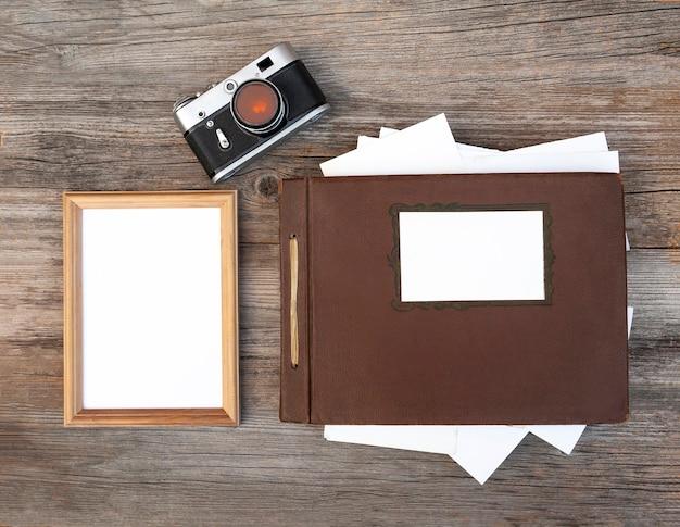 Marco vacío con cámara retro y álbum de fotos sobre una mesa de madera.