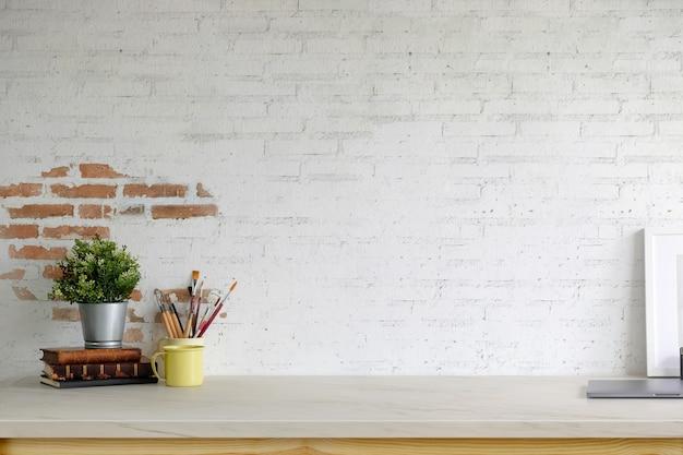 Marco vacío del cartel de la maqueta, suministros de oficina y espacio de copia en la tabla de espacio de trabajo