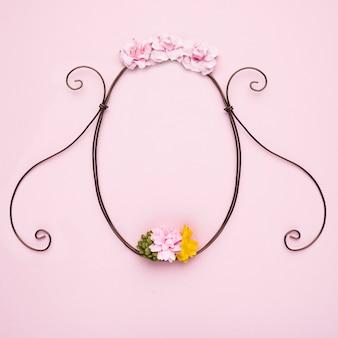 Marco vacío decorativo de flores hechas a mano sobre fondo rosa