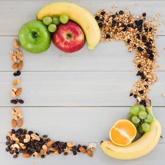 Un marco vacío hecho con frutos secos; avena y frutas en mesa de madera.
