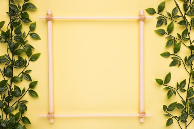 Marco vacío de madera sobre papel amarillo con hojas artificiales verdes