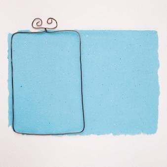 Marco vacío metálico sobre papel azul sobre fondo blanco.