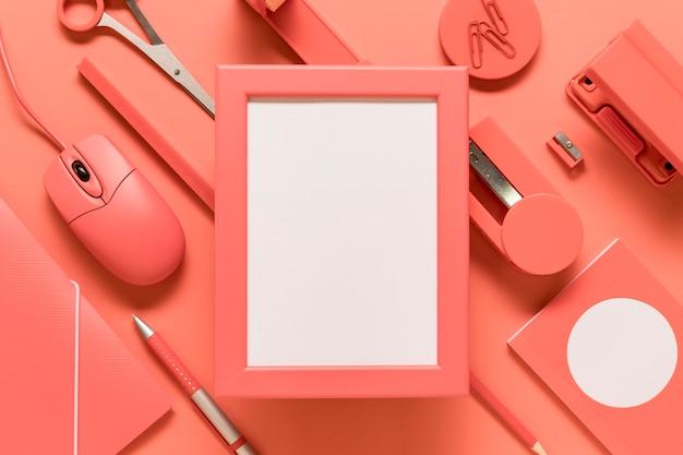 Marco vacío y suministros de oficina en superficie coloreada