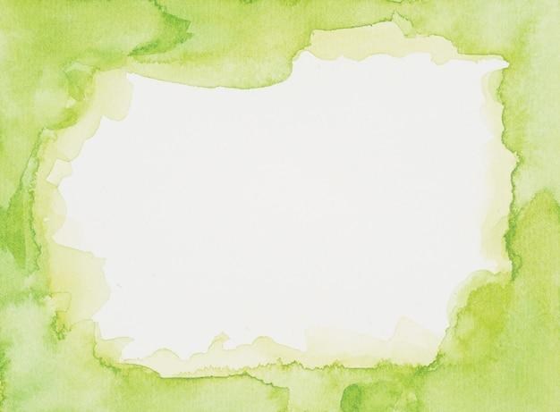 Marco verde de pinturas sobre hoja blanca.