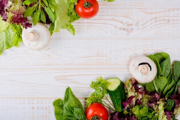Marco de verduras frescas, lechuga, tomate, pepino, champiñones, perejil, espinacas en una madera blanca