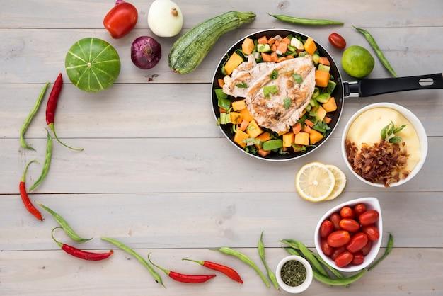 Marco de verduras saludables y sartén frita con carne.