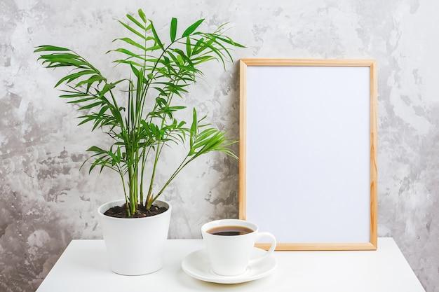 Marco vertical de madera con tarjeta blanca en blanco, taza de café y flor de palma exótica verde en maceta en la mesa sobre muro de hormigón gris