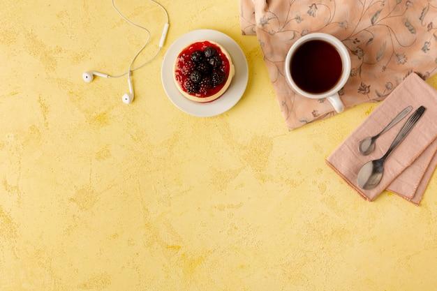 Marco de vista superior con comida y auriculares sobre fondo amarillo