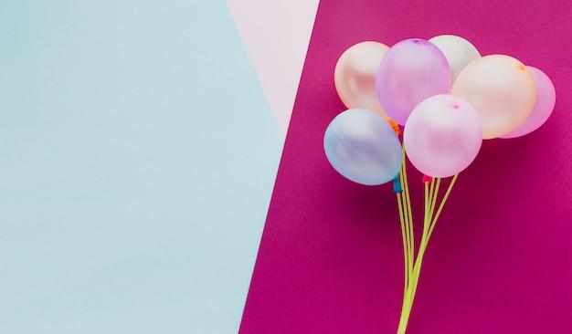 Marco de vista superior con globos y fondo rosa