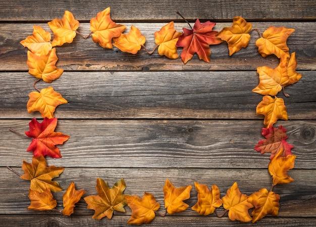 Marco de vista superior con hojas coloridas en mesa de madera