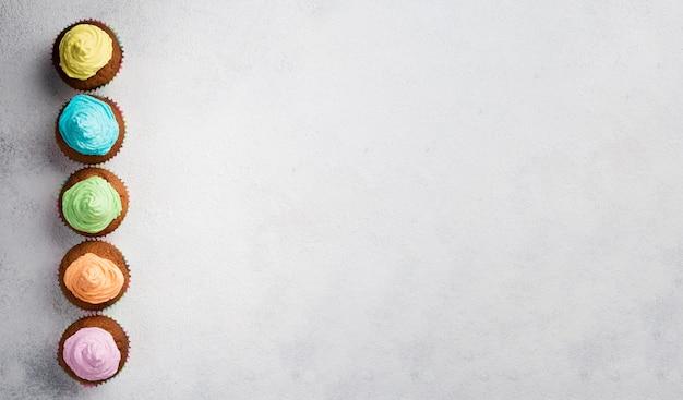 Marco de vista superior con magdalenas coloridas y espacio de copia