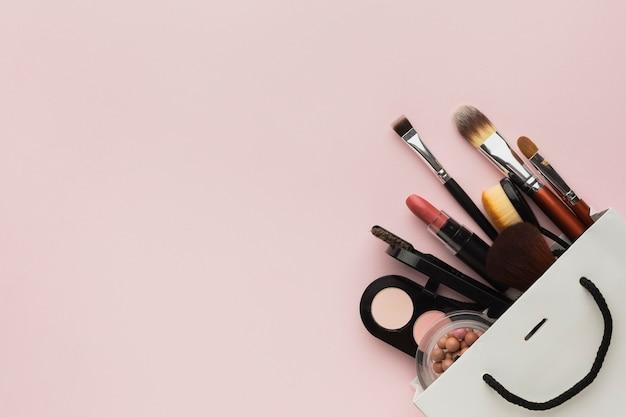 Marco de vista superior con productos de maquillaje en una bolsa