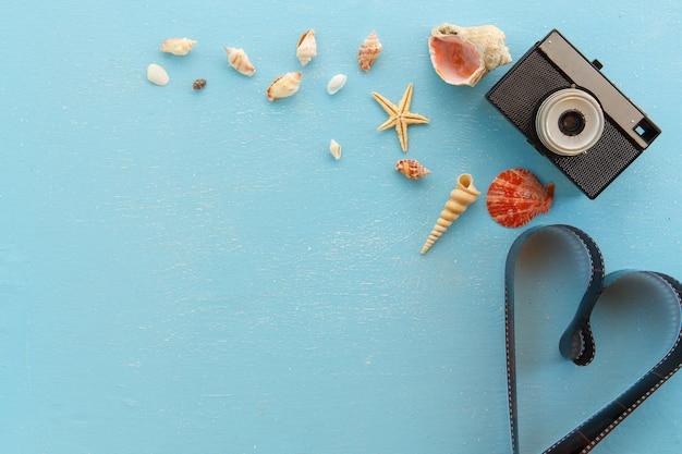 Marcos de fotos de papel en blanco con estrellas de mar, conchas y artículos sobre la mesa de madera.