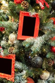 Marcos de fotos vintage rojos con espacio para texto colgado en el árbol de navidad de cerca