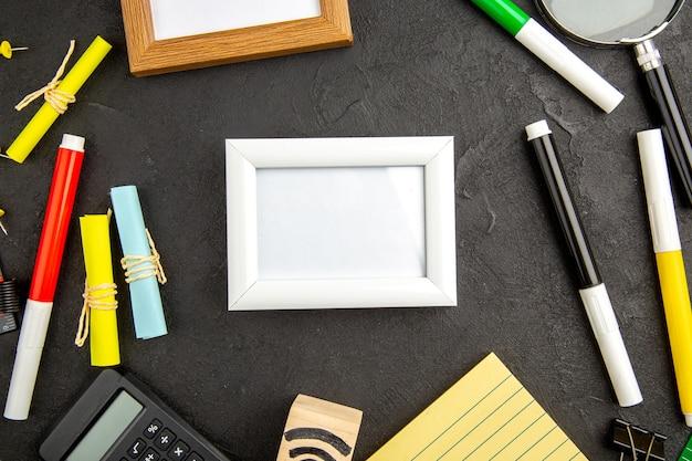 Marcos de fotos de vista superior con lápices de colores sobre fondo oscuro dibujo a color de arte bloc de notas bolígrafo colegio cuaderno escuela
