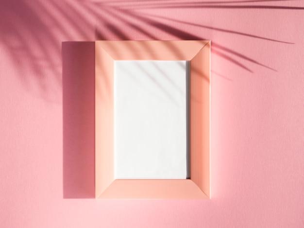 Marcos de retrato de rosa sobre un fondo rosa con una sombra de hoja de palma