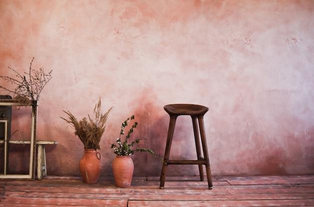 Marcos vacíos, silla de madera, jarras de barro con ramas en rústica sala vintage