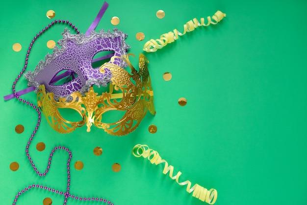 Mardi gras, concepto de carnaval. máscara morada y dorada con cuentas, confeti