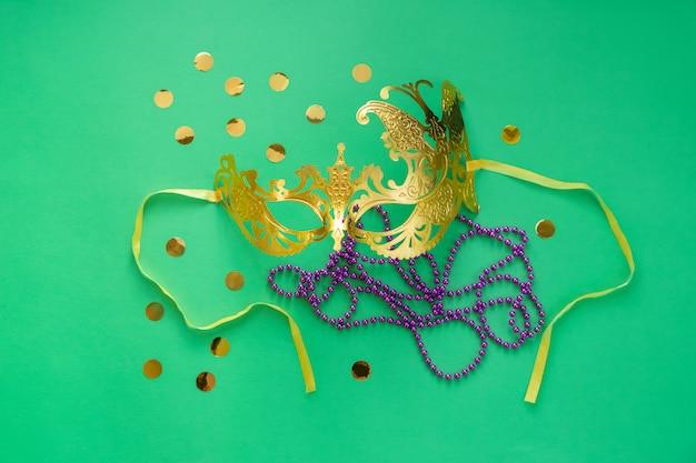 Mardi gras, concepto de carnaval. máscara de oro con cuentas y confeti.