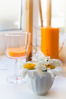 Margaritas blancas se paran en el alféizar de la ventana junto a las velas