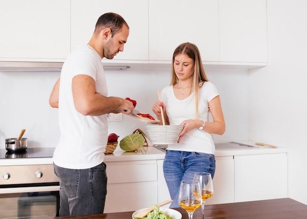 Marido ayudando a su esposa para cocinar comida en la cocina.