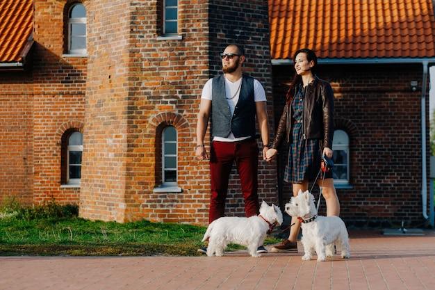 Marido con una bella esposa paseando a sus perros blancos en la calle