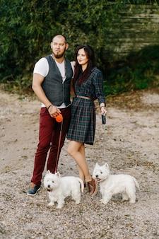 Marido con una bella esposa paseando a sus perros blancos en el parque