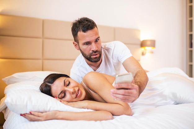 Marido celoso espiando el teléfono de su pareja mientras ella duerme en una cama en su casa.
