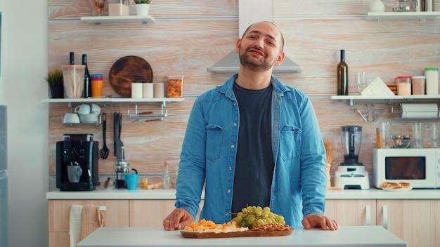 Marido charlando en la cocina mientras su familia prepara la cena en segundo plano. retrato feliz sonriente joven mirando a la cámara, retrato de disparo a la cabeza, comiendo queso, familia extendida a su alrededor