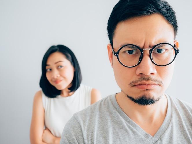 Marido enojado y molesto asiático con concepto de argumento esposa feliz y obstinada