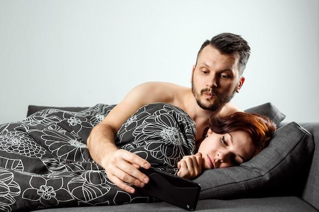 El marido espía en el teléfono de su esposa mientras ella duerme.