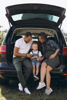 Marido con esposa embarazada y su hijo sentado en carro