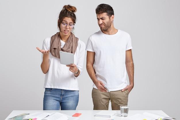 Marido y esposa joven parados juntos en el escritorio