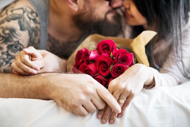 Marido esposa sorprendida con ramo de rosas rojas