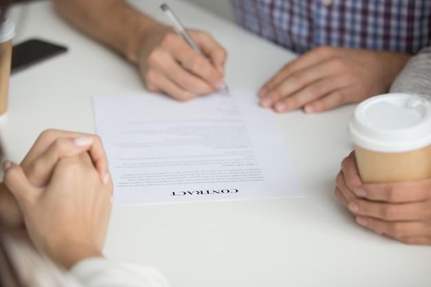 Marido firma contrato de compra de vivienda.