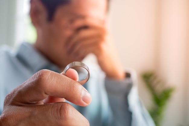 Marido llorando tristemente sosteniendo un anillo de bodas después de una discusión con su esposa y decidiendo separarse