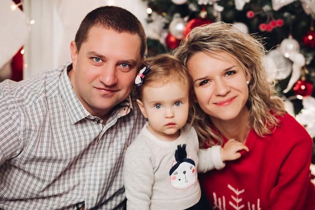 Marido y mujer besándose en el sofá con pequeña hija en regalos por árbol de navidad.