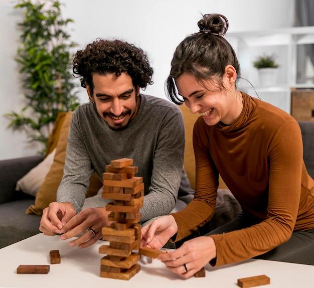 Marido y mujer jugando un juego de torre de madera en casa