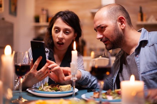 Marido y mujer mirando conmocionados por teléfono mientras tienen una cena romántica en la cocina adultos sentados a la mesa en la cocina navegando, buscando, usando teléfonos inteligentes, internet, celebrando el aniversario.