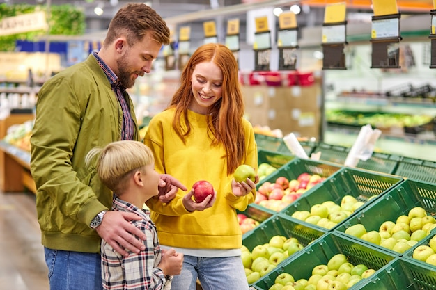 Marido y mujer con un niño compran frutas, manzanas. familia de tres personas eligiendo manzana fresca en el departamento de frutas de supermercado o mercado