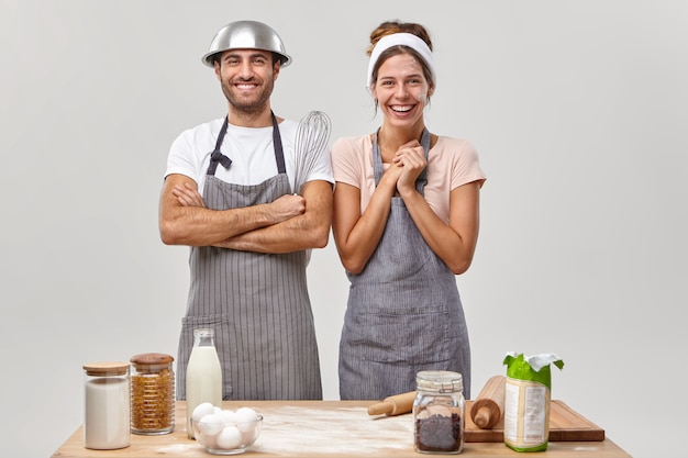 Marido y mujer posan en la cocina preparando una sabrosa cena